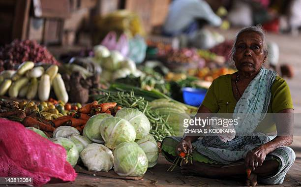A Sri Lankan Tamil vendor looks from her stand at a vegetable market in Jaffna on May 4 2012 Sri Lanka recorded an impressive 83 percent growth rate...