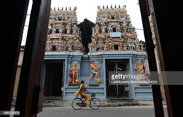 A Sri Lankan Tamil woman cycles past a Hindu temple in Jaffna 400 kilometres north of the capital Colombo on November 15 2013 British Prime Minister...