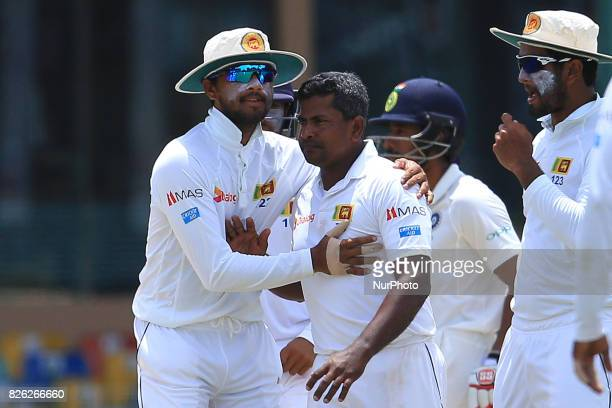 Sri Lankan test cricket captain Dinesh Chandimal hugs Rangana Herath after Herath dismissed Indian cricketer Ravichandran Ashwin during the 2nd Day's...