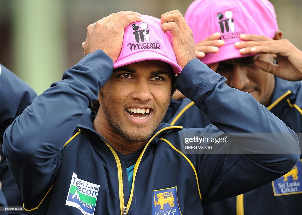 Sri Lankan Test cricketer Dinesh Chandimal (C) tries on a 'Baggy Pink' cap in aid of the McGrath Foundation, prior to a team photo at the Sydney Cricket Ground on the eve of the third cricket Test between Sri Lanka and Australia in Sydney on January 2, 2013. IMAGE AFP PHOTO / Greg WOOD