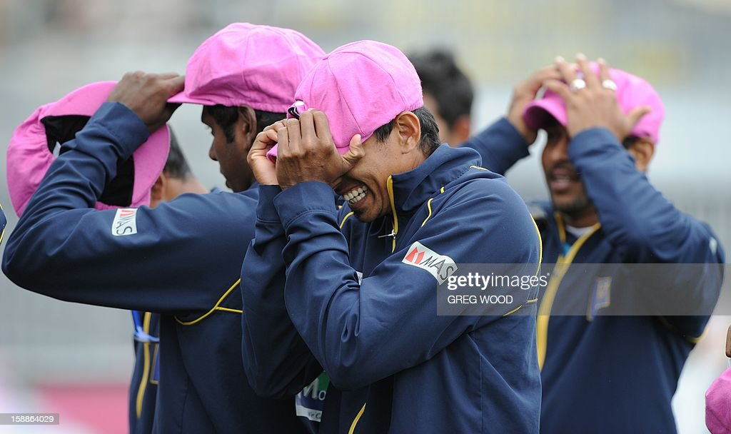 Sri Lankan Test cricketers try on 'Baggy Pink' caps in aid of the McGrath Foundation, prior to a team photo at the Sydney Cricket Ground on the eve of the third cricket Test between Sri Lanka and Australia in Sydney on January 2, 2013. IMAGE AFP PHOTO / Greg WOOD