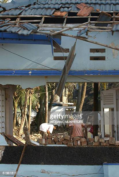 Sri Lankan tsunami victims clear rubble from their destroyed house at Hambantota some 235 kms south of Colombo 14 January 2005 Sri Lankans devastated...