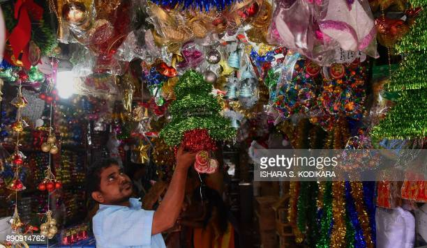 A Sri Lankan vendor arranges decorations for sale in a market ahead of Christmas Day in Colombo on December 12 2017 / AFP PHOTO / ISHARA S KODIKARA