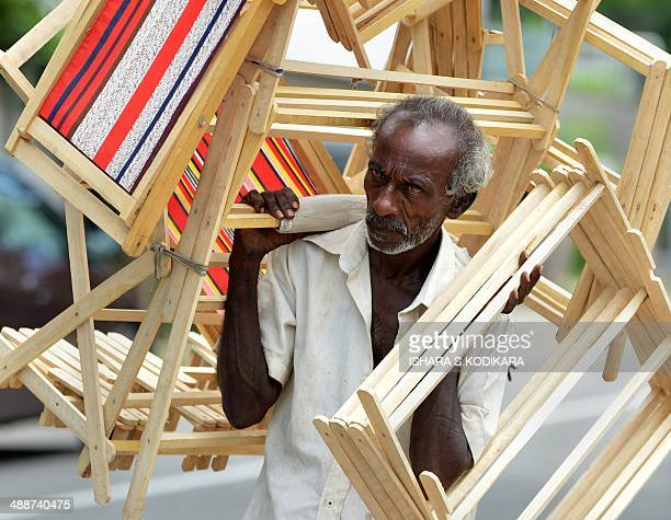 A Sri Lankan vendor carries clothes racks for sale on a street in Colombo on May 8 2014 Sri Lanka's economy recorded 80 percentplus growth for two...
