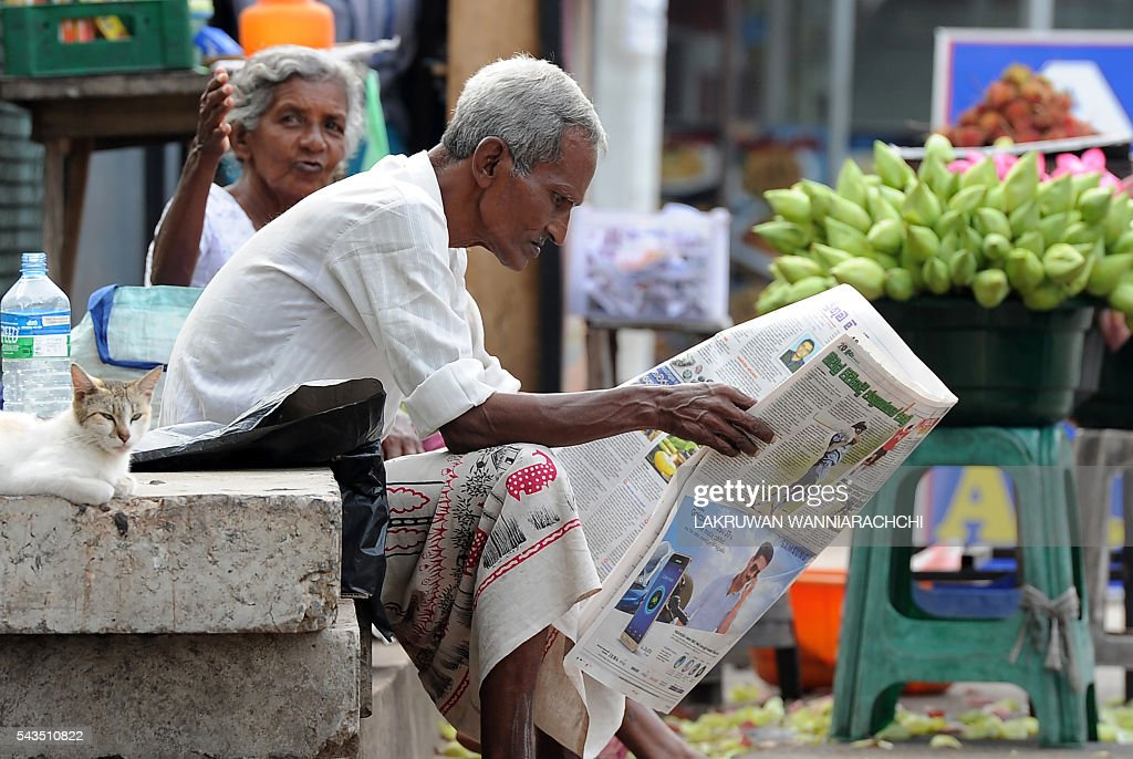 A Sri Lankan vendor reads a newspaper at a market in Colombo on June 29, 2016. / AFP / LAKRUWAN