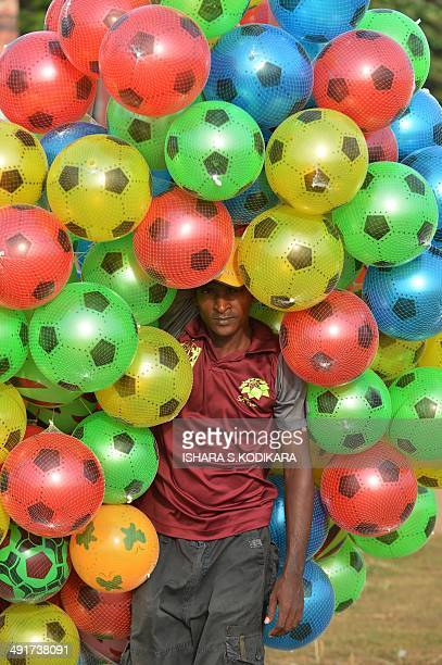 A Sri Lankan vendor sell toy balls on the Galle Face promenade in the center of the Sri Lankan capital of Colombo on May 17 2014 Sri Lanka's economy...