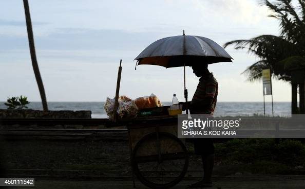 A Sri Lankan vendor sells popcorn and corn in Colombo on June 5 2014 Sri Lanka's economy recorded 80 percentplus growth for two straight years after...