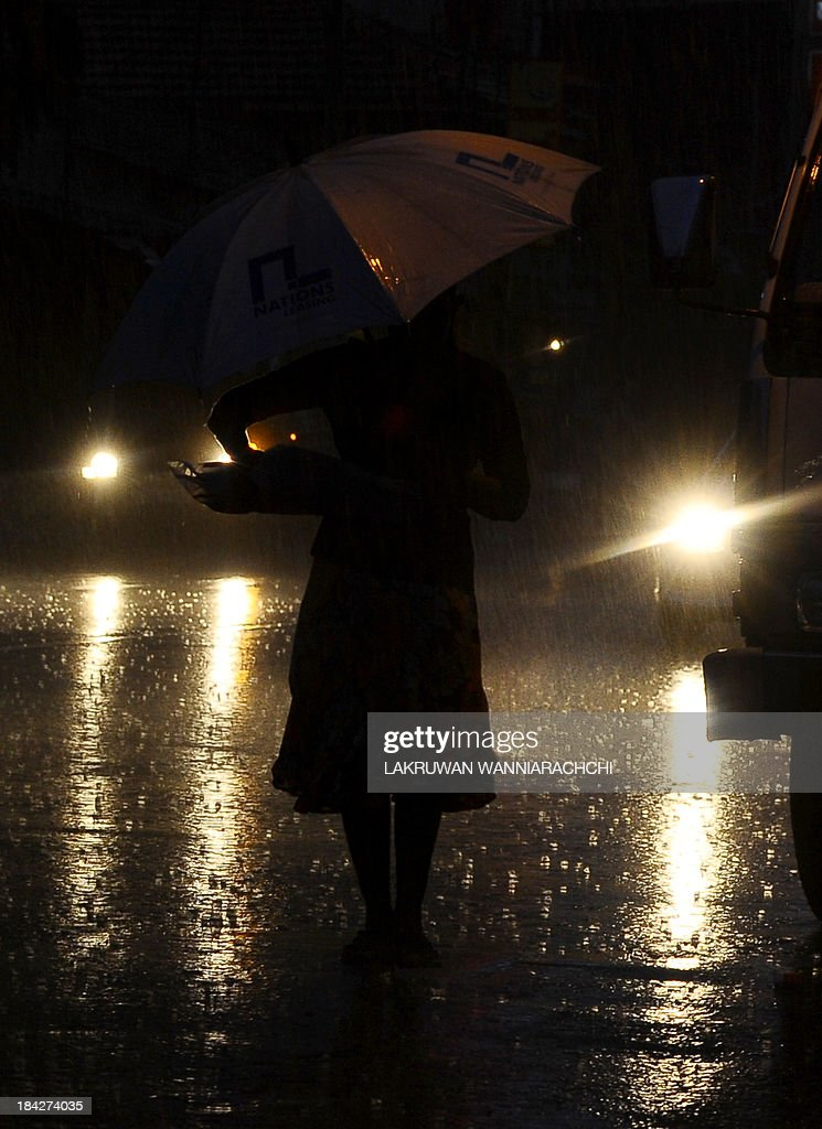 A Sri Lankan vendors shelters from the rain under an umbrella at a Sunday market in Colombo on October 13, 2013. The IMF expects growth for the current calendar year to be about 6.5 percent, a full percentage point lower than Sri Lanka's central bank's forecast of 7.5 percent.