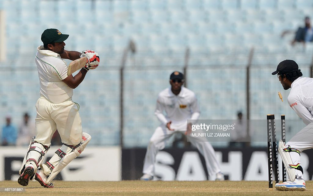 Sri Lankan wicketkeeper Dinesh Chandimal breaks the stumps as Bangladesh batsman Imrul Kayes tries to make his ground during the third day of the...