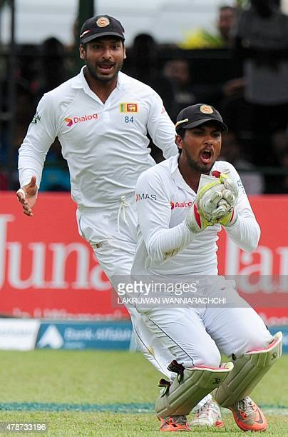 Sri Lankan wicketkeeper Dinesh Chandimal takes the catch to dismiss Pakistan cricketer Ahmed Shehzad as teammate Kumar Sangakkara looks on during the...