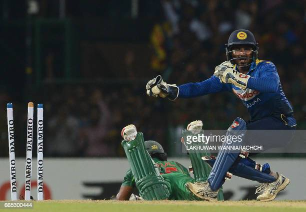Sri Lankan wicketkeeper Kusal Perera successfully attempts to run out Bangladesh cricketer Imrul Kayes during the second T20 international cricket...