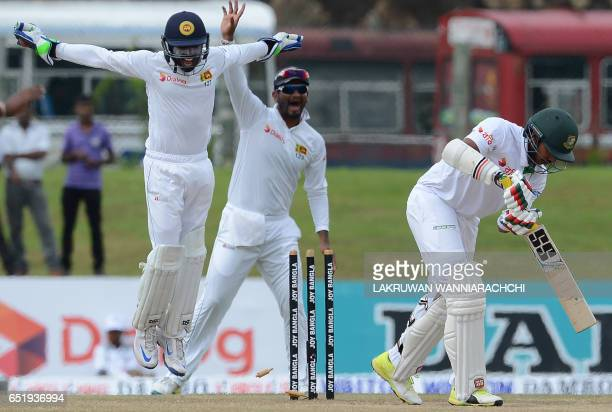 Sri Lankan wicketkeeper Niroshan Dickwella and Dimuth Karunaratne celebrates after he dismissed Bangladesh cricketer Soumya Sarkar during the final...