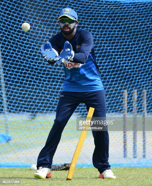 Sri Lankan wicketkeeper Niroshan Dickwella catches a ball during a practice session at Galle International Cricket Stadium in Galle on June 28 2017...