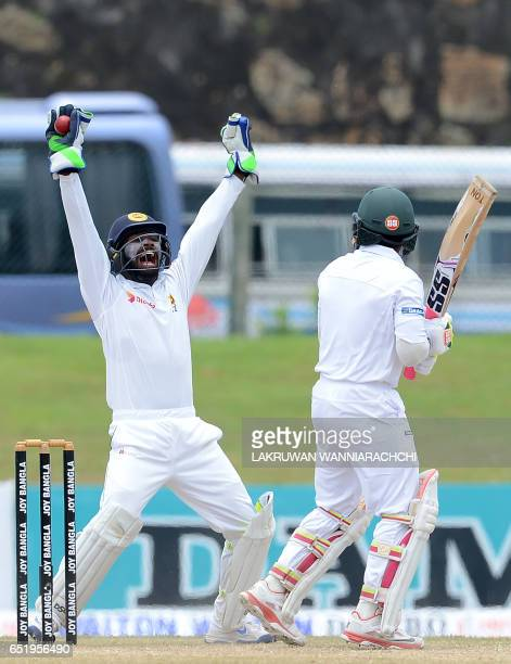 Sri Lankan wicketkeeper Niroshan Dickwella celebrates after Bangladesh cricket captain Mushfiqur Rahim was dismissed during the final day of the...