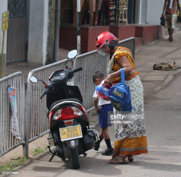 Sri Lankan woman carries his son's school bag near the motorcycle in Colombo the capital of Sri Lanka on July 10 2017 An island country Sri Lanka is...