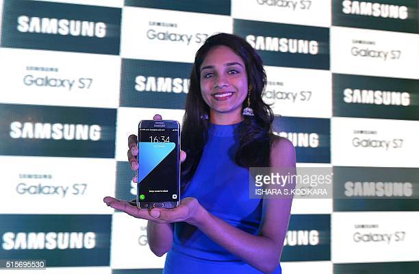 A Sri Lankan woman holds up Samsung Electronics' latest flagship smartphone the Galaxy S7 edge during a launch in Colombo on March 15 2016 / AFP /...
