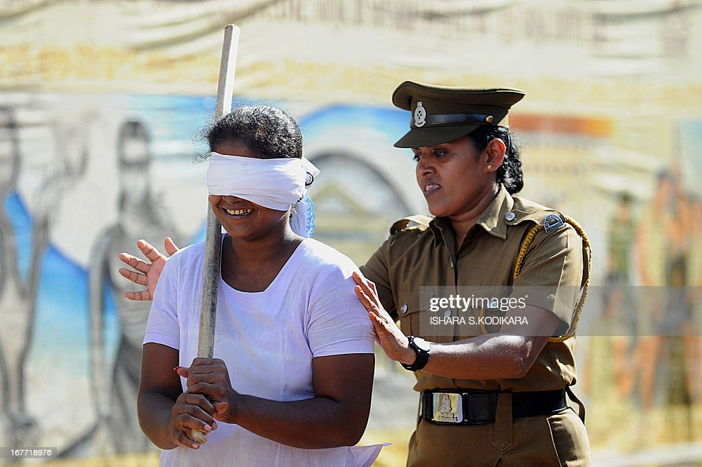 A Sri Lankan woman prisoner is guided by a guard as she takes part in an event that consists of breaking a hanging pot with a stick while blindfolded to celebrate the Sinhalese and Tamil New Year at a prison complex in Colombo on April 28, 2013. The Sinhalese and Tamil New Year dawned on April 14, but traditional games are organised across the island to celebrate the occasion for weeks to come. AFP PHOTO / Ishara S