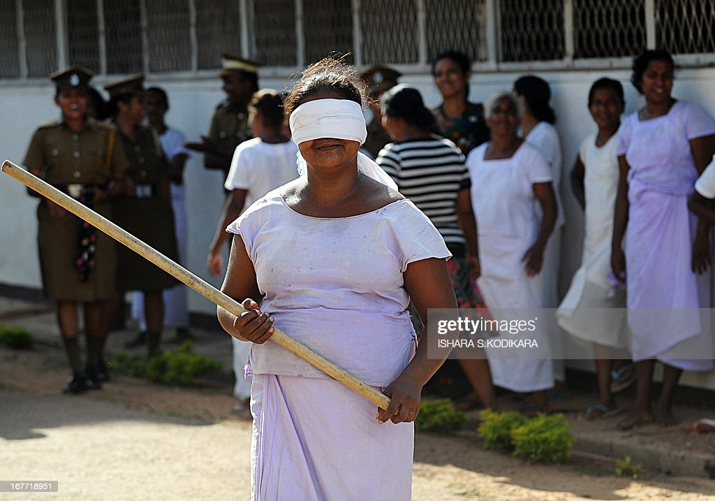 A Sri Lankan woman prisoner prepares to take part in an event that consists of breaking a hanging pot with a stick while blindfolded to celebrate the Sinhalese and Tamil New Year at a prison complex in Colombo on April 28, 2013. The Sinhalese and Tamil New Year dawned on April 14, but traditional games are organised across the island to celebrate the occasion for weeks to come. AFP PHOTO / Ishara S