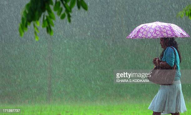 A Sri Lankan woman shelters under an umbrella as she walks through a heavy downpour in Colombo on June 24 2013 The Sri Lankan capital has been lashed...