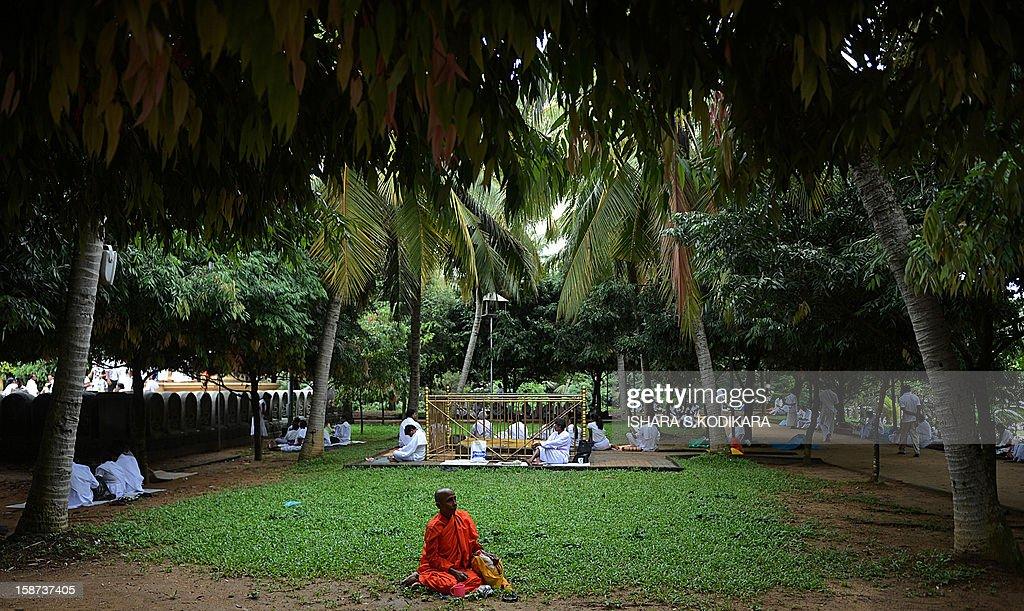 A Sri Lankan woman sits in a courtyard during Poya, a full moon religious festival, at the Kelaniya Temple in Kelaniya on December 27, 2012. The predominantly Buddhist Island nation marks every full moon as a key religious holiday. AFP PHOTO/ Ishara S. KODIKARA