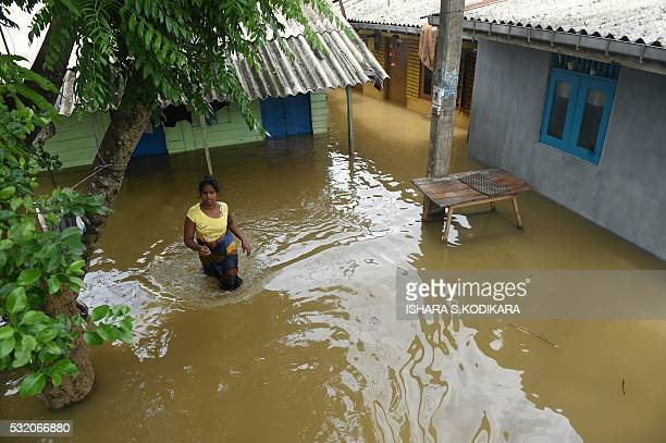 A Sri Lankan woman wades through floodwaters in Kelaniya suburb of the capital Colombo on May 18 2016 Rescue workers on May 18 recovered the bodies...