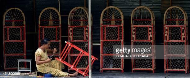 A Sri Lankan woman works on furniture made of rattan in the village of Radawadunna on August 28 2014 Sri Lanka's economy recorded 80 percentplus...