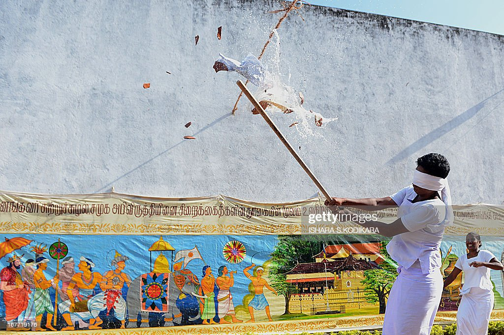 Sri Lankan women prisoners take part in an event that consists of breaking a hanging pot with a stick while blindfolded to celebrate the Sinhalese and Tamil New Year at a prison complex in Colombo on April 28, 2013. The Sinhalese and Tamil New Year dawned on April 14, but traditional games are organised across the island to celebrate the occasion for weeks to come. AFP PHOTO / Ishara S