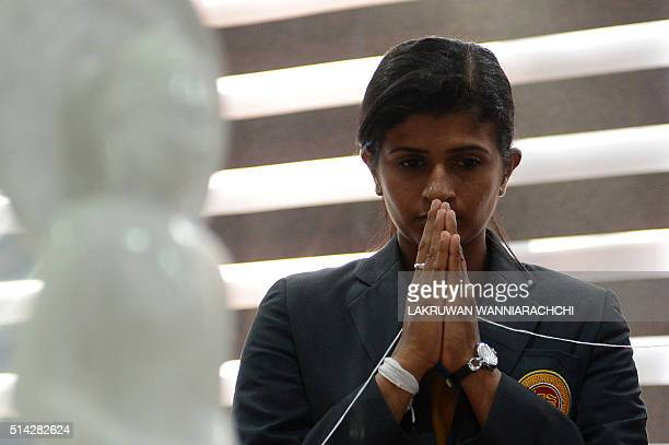 Sri Lankan women's cricket team captain Shashikala Siriwardana watches as Sri Lankan Buddhist monks bless the team in Colombo on March 8 2016 ahead...