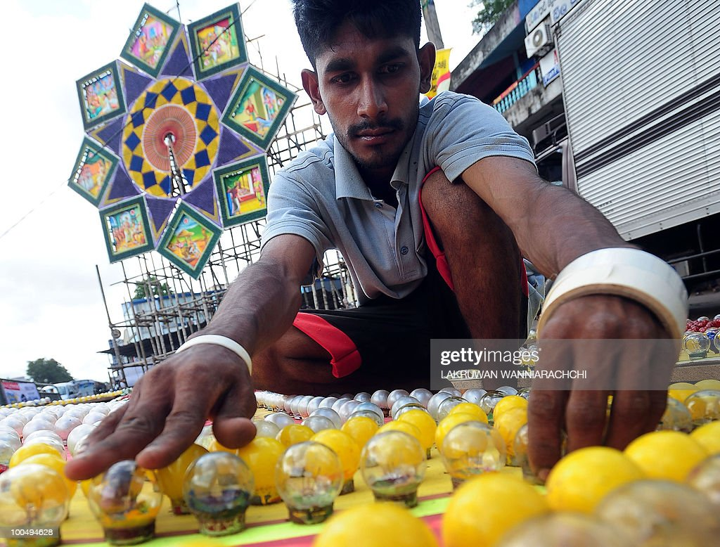 A Sri Lankan worker adjusts lightbulbs on a pandal, a coloured structure that is illuminated with bulbs, in Colombo on May 25, 2010, ahead of the key Buddhist festival of Wesak. Buddhists commemorates the birth of Buddha, his attaining enlightenment and his passing away on the full moon day of May which falls on May 27 this year. AFP PHOTO/ Lakruwan WANNIARACHCHI