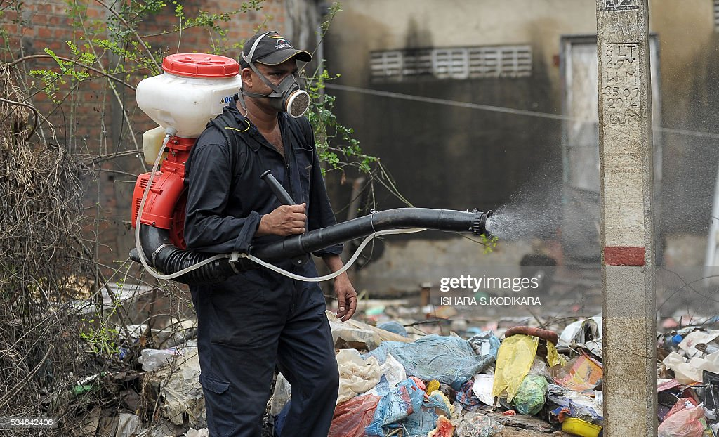A Sri Lankan worker sprays a flood-affected home on the edge of the Sri Lankan capital Colombo on May 27, 2016, days after water levels subsided allowing thousands of residents to return home. The heaviest rains in nearly 25 years had forced some 650,000 from their homes, according to the finance ministry and left another 102 dead and 100 missing following floods and landslides. / AFP / ISHARA