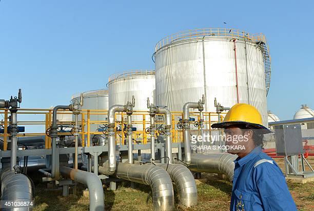A Sri Lankan worker walks past 76 million dollar oil tank farm at the southern deep sea port of Hambantota on June 22 2014 Sri Lanka is hoping its...