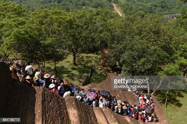 TOPSHOT Sri Lankans and foreign tourists climb the 80metre fortress of Sigiriya rock in Sigiriya northcentral Sri Lanka on February 11 2017 The...