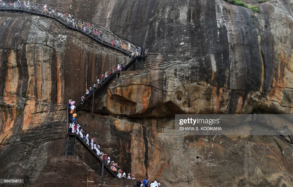 TOPSHOT - Sri Lankans and tourists climb the 80-metre (600-foot) fortress of Sigiriya rock (the Lion Rock) in Sigiriya, north-central Sri Lanka, on February 11, 2017. The Sigiriya rock, 160 kilometres (100 miles) north of Colombo, is a World Heritage site known for frescoes of bare-chested women. The number of foreign tourists visiting Sri Lanka has swelled since the island ended a 37-year separatist conflict with Tamil Tiger rebels in May 2009. / AFP PHOTO / Ishara S. KODIKARA