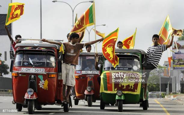 Sri Lankans wave the national flag as they celebrate their country's military victory in Colombo on May 18 2009 Tamil Tiger leader Velupillai...