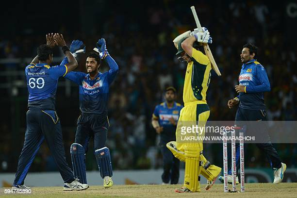 Sri Lanka's Angelo Mathews celebrates with his teammates after he dismissed Australia's Travis Head during the second oneday International cricket...