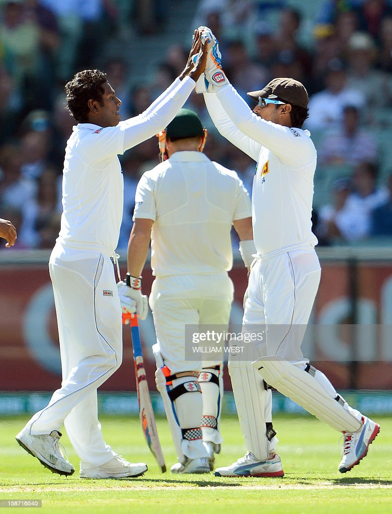 Sri Lanka's Angelo Mathews (L) is congratulated by teammate Kumar Sangakkara (R) after dismissing Australian batsman David Warner (C) on the first day of the second cricket Test match at the Melbourne Cricket Ground (MCG), in Melbourne, on December 26, 2012. AFP PHOTO/William WEST IMAGE RESTRICTED TO EDITORIAL USE - STRICTLY NO COMMERCIAL USE