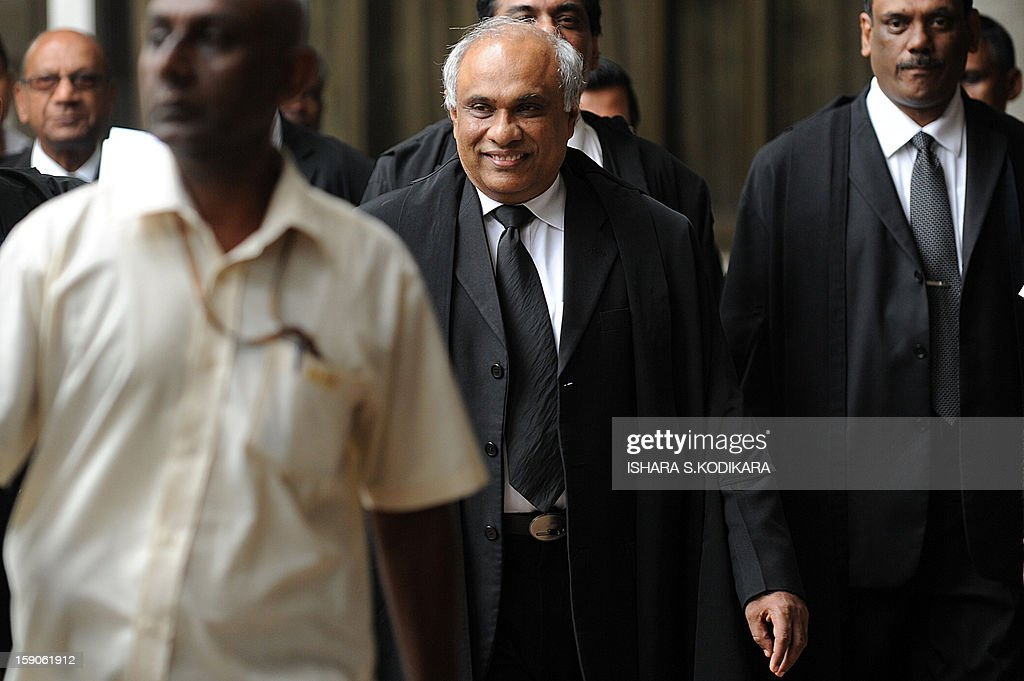 Sri Lanka's attorney general, Palitha Fernando (C) arrives at the Supreme Court complex for a hearing into a challenge against parliament's attempt to impeach the country's chief justice, Shirani Bandaranayake in the capital Colombo on January 7, 2013. The court held that a parliamentary process used to find the top judge guilty of professional and personal misconduct was illegal and asked the legislature to stop its move to sack the chief judge. AFP POHOTO/ Ishara S