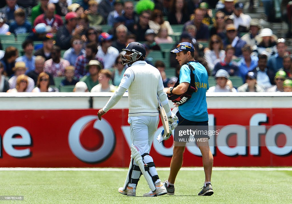 Sri Lanka's batsman Kumar Sangakkara (L) walks off after injuring his hand in a delivery from Australia's fast bowler Mitchell Johnson as Australia defeats Sri Lanka on the third day of the second cricket Test match at the Melbourne Cricket Ground (MCG) on December 28, 2012. AFP PHOTO/William WEST USE