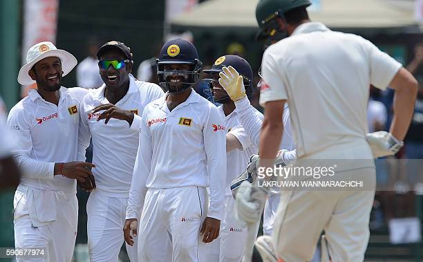 Sri Lanka's captain Angelo Mathews celebrates with teammates after he dismissed Australia's Moises Henriques during the final day of the third and...