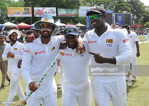 Sri Lanka's captain Angelo Mathews celebrates with teammates Rangana Herath and Dinesh Chandimal after victory in the third and final Test match...