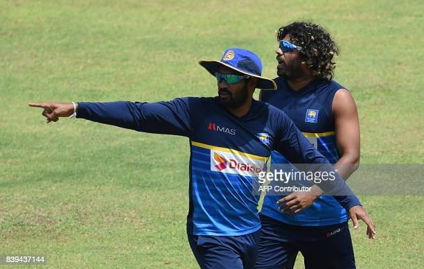 Sri Lanka's captain Chamara Kapugedera and Lasith Malinga take part in a practice session at the Pallekele International Cricket Stadium in Pallekele...