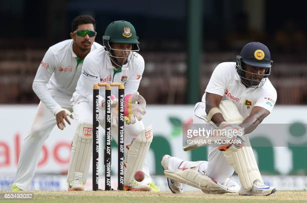 Sri Lanka's captain Rangana Herath plays a shot as Bangladesh captain Mushfiqur Rahim looks on during the first day of the second and final Test...