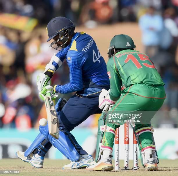 Sri Lanka's captain Upul Tharang plays a shot as Bangladesh wicketkeeper Mushfiqur Rahim looks on during the second One Day International cricket...