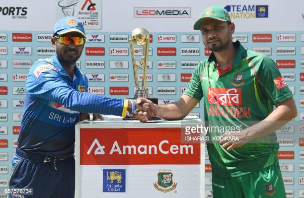 Sri Lanka's captain Upul Tharanga and Bangladesh captain Mashrafe Mortaza shake hands as they pose with the series trophy ahead of the first one day...