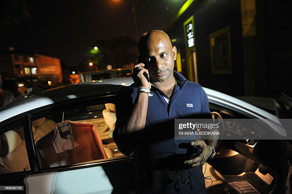 Sri Lanka's chief cricket selector Sanath Jayasuriya speaks on his mobile phone as he leaves the Sri Lankan Cricket Board offices in Colombo after a meeting with selectors on March 3, 2013. Sri Lanka's national cricketers dropped a controversial pay demand today, clearing the way for them to play against Bangladesh in an upcoming series, a top official said. Chief Selector Sanath Jayasuriya said he held crisis talks with the rebellious players who agreed to the same terms and conditions offered by Sri Lanka Cricket (SLC) and would be available for selection for the first Test starting March 8. AFP PHOTO / Ishara S.KODIKARA