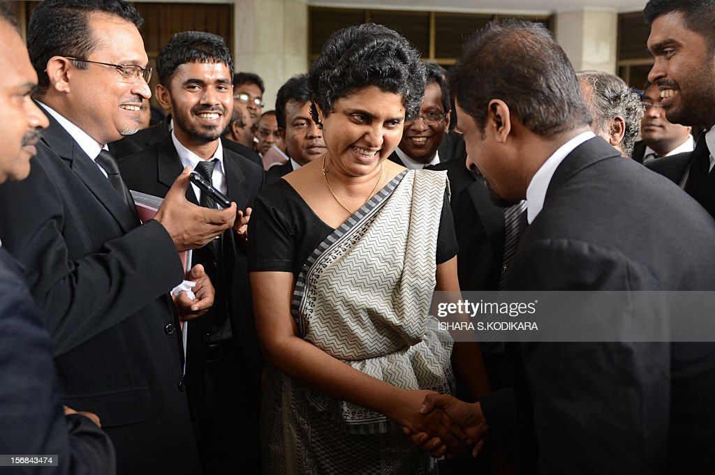 Sri Lanka's Chief Justice Shirani Bandaranayake (C) shakes hands with an unidentified man as she walks out of the Supreme Court in Colombo on November 23, 2012 as lawyers see her off as she travels to the national parliament to face impeachment proceedings. Bandaranayake faces 14 allegations of financial and official misconduct after the supreme court gave rulings that were seen as unfavourable for the government of President Mahinda Rajapakse. AFP PHOTO/Ishara S. KODIKARA