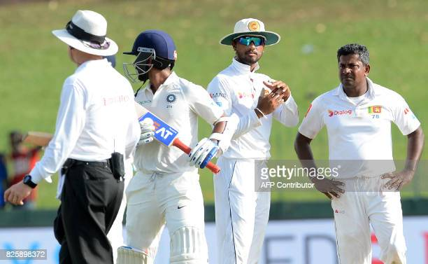 Sri Lanka's cricket team captain Dinesh Chandimal signals for third umpire review for succesful wicket of Indian cricketer Ajinkya as teammate...