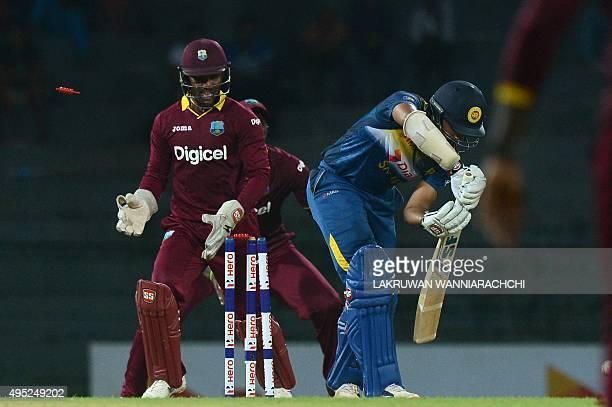 Sri Lanka's Cricketer Danushka Gunathilaka gets dismissed by West Indies Cricketer Sunil Narine as wicketkeeper Denesh Ramdin looks on during the...