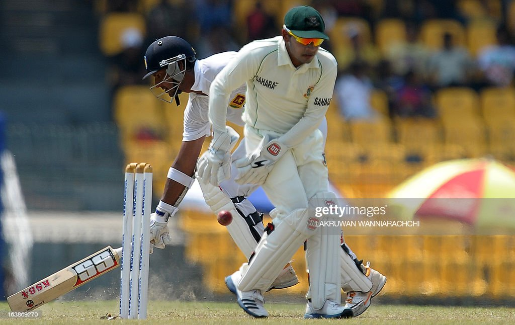 Sri Lanka's cricketer Kumar Sangakkara (L) avoids a run out attempt as Bangladeshi wicketkeeper and captain Mushfiqur Rahim tries to control the ball during the second day of their second Test match between Sri Lanka and Bangladesh at the R. Premadasa Cricket Stadium in Colombo on March 17, 2013.