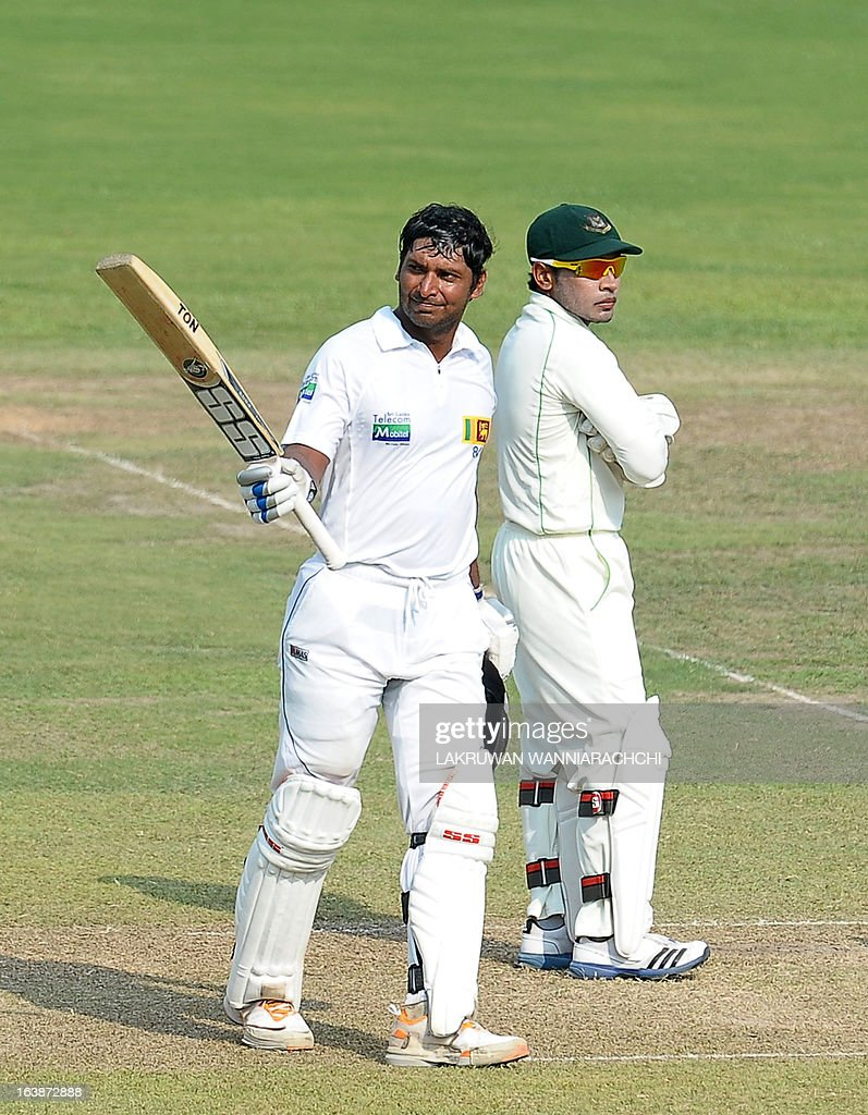 Sri Lanka's cricketer Kumar Sangakkara (L) raises his bat in celebration after scoring a century (100 runs) as Bangladeshi wicketkeeper and captain Mushfiqur Rahim look on during the second day of their second Test match between Sri Lanka and Bangladesh at the R. Premadasa Cricket Stadium in Colombo on March 17, 2013.